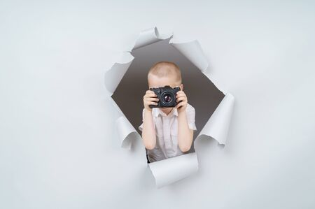 Child boy with retro compact camera and emerging through torn paper hole in studio, has excited cheerful expression, looks through gray background., isolated on gray background. Stok Fotoğraf