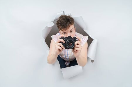 Pretty woman paparazzi with retro compact camera emerging through torn paper hole in studio, has excited cheerful expression, isolated on gray background.