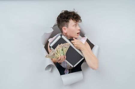 Pretty Woman is holding a suitcase full of money and emerging through torn paper hole in studio, has excited cheerful expression, looks through breakthrough of gray background.