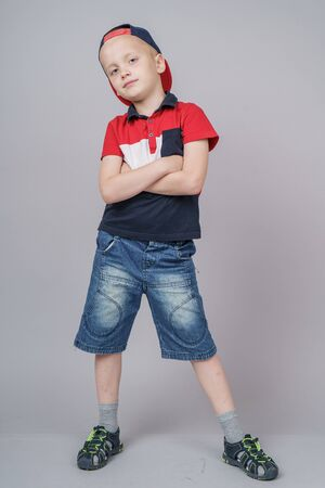 Young pretty boy posing at studio as a fashion model. Photo of preschooler 7 years old over gray background