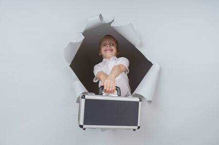 Cool boy is holding a suitcase full of money and emerging through torn paper hole in studio, has excited cheerful expression, looks through breakthrough of gray background.