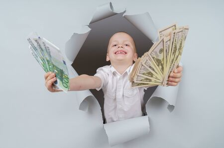 Cool boy is holding a pack of dollars and emerging through torn paper hole in studio, has excited cheerful expression, looks through breakthrough of gray background.