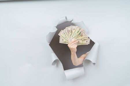 Pretty Woman is holding a pack of dollars and emerging through torn paper hole in studio, has excited cheerful expression, looks through breakthrough of gray background.