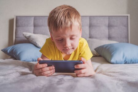 Distance education, learning. Boy is lying on the bed with a smartphone in the room. Child with a gadget. Teenage child using smartphone.