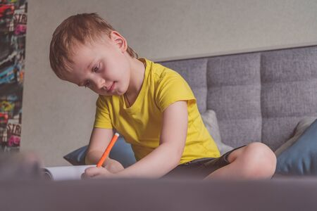 Young caucasian boy draws in an album, writes on paper at home sitting on bed.
