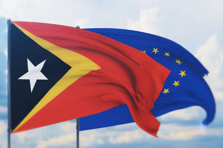 Waving European Union flag and flag of East Timor. Closeup view, 3D illustration.