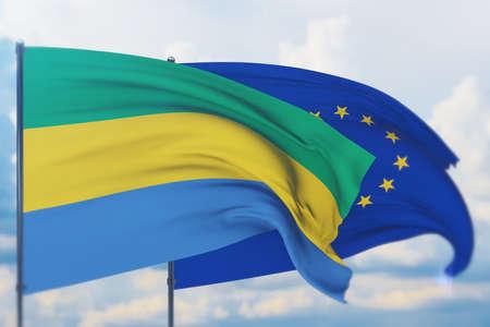 Waving European Union flag and flag of Gabon. Closeup view, 3D illustration. Фото со стока