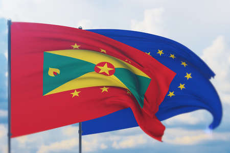 Waving European Union flag and flag of Grenada. Closeup view, 3D illustration. Фото со стока