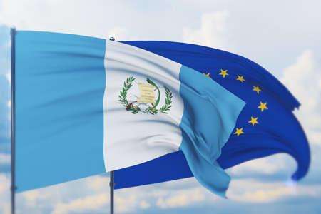 Waving European Union flag and flag of Guatemala. Closeup view, 3D illustration. Фото со стока