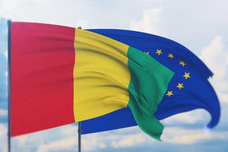 Waving European Union flag and flag of Guinea. Closeup view, 3D illustration.