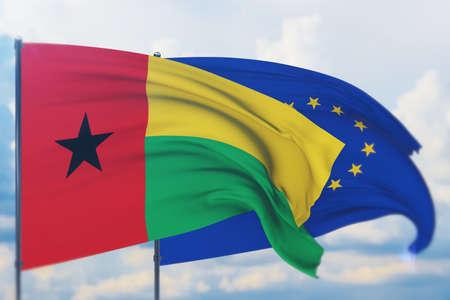 Waving European Union flag and flag of Guinea-Bissau. Closeup view, 3D illustration. Фото со стока