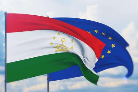 Waving European Union flag and flag of Tajikistan. Closeup view, 3D illustration. Фото со стока