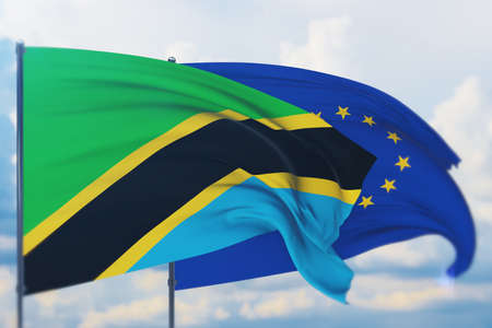 Waving European Union flag and flag of Tanzania. Closeup view, 3D illustration.
