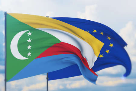 Waving European Union flag and flag of Comoros. Closeup view, 3D illustration. Фото со стока