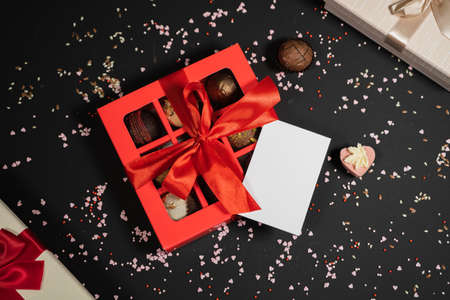 Handmade chocolate truffle candies in a red box on a dark background. Directly above top view. Фото со стока