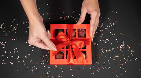 Various handmade chocolate truffle candies in a red box on a dark background in female hands. Фото со стока