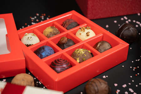 Various handmade chocolate truffle candies in a red box on a dark background. Close up view.