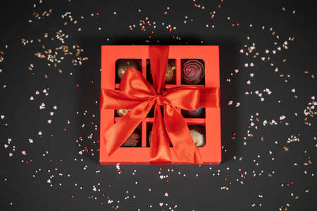Various handmade chocolate truffle candies in a red box on a dark background. Directly above top view.