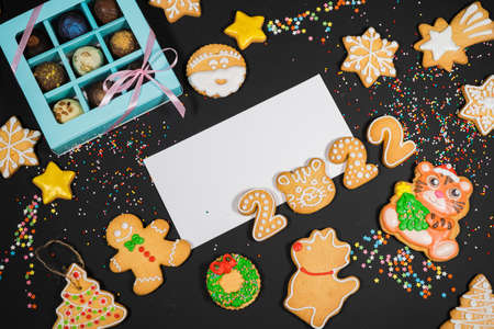 Christmas background with gingerbread on gray surface. Holiday mood card. Top view, copy space. Family traditions, DIY, celebration concept. Festive background with homemade gingerbread cookies. Фото со стока
