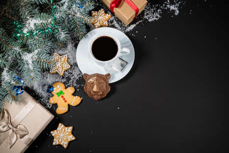 Christmas and New Year decoration composition. Top view of fur-tree branches on dark background with place for your text. Cups of fragrant coffee with gingerbread and chokolate. Фото со стока