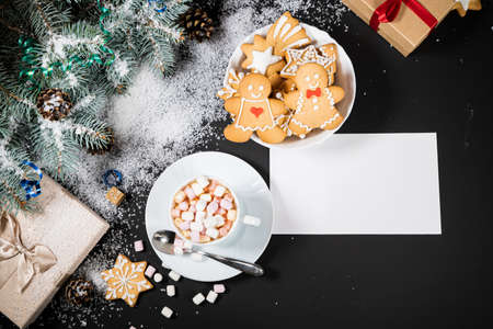 Christmas and New Year decoration composition. Top view of fur-tree branches on dark background with place for your text. Cups of fragrant coffee with marshmallows, gingerbread and chokolate. Фото со стока