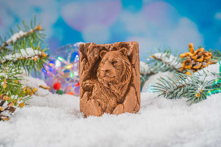 Christmas chocolate toy on snow. Chocolate toy in the shape of a tiger, symbol of the year 2022. Joyful mood.