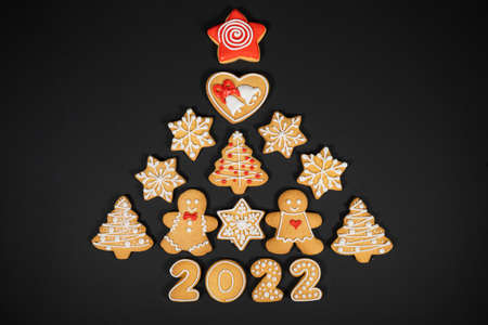 Christmas tree made from gingerbread cookies on dark black background with copy space for text. Holiday, celebration and cooking concept. New year and christmas postcard. Фото со стока