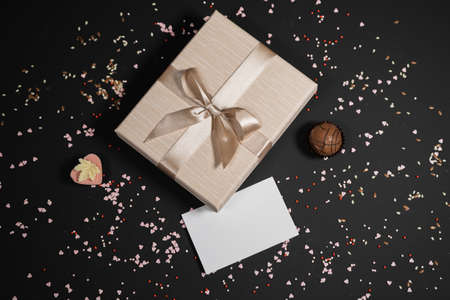 Handmade chocolate truffle candies in a beige box on a dark background. Directly above top view. Фото со стока