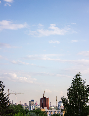 Multi-storey residential building under construction and a crane on a background of blue sky Stok Fotoğraf