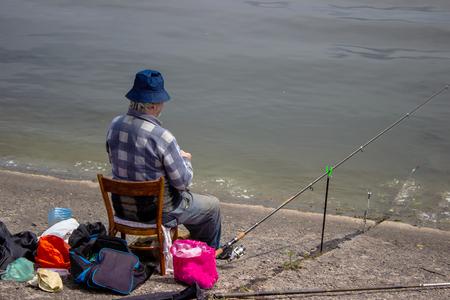 man sitting near the water fishing