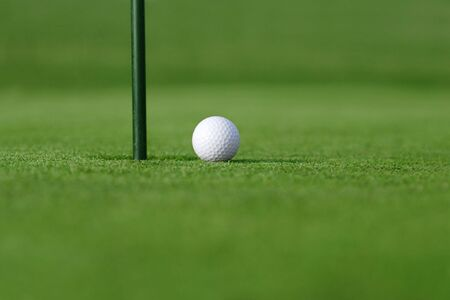 friendly competition: so close  golf ball near hole