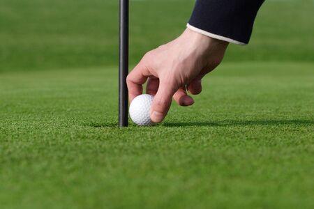 bad temper: so close man picking up golf ball