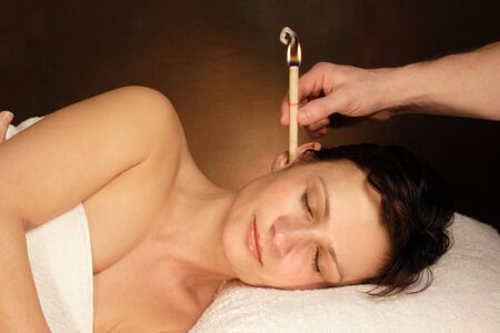 deafness: woman with ear candle therapy Stock Photo