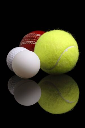 cricket ball: variety of sports balls on a reflective surface Stock Photo