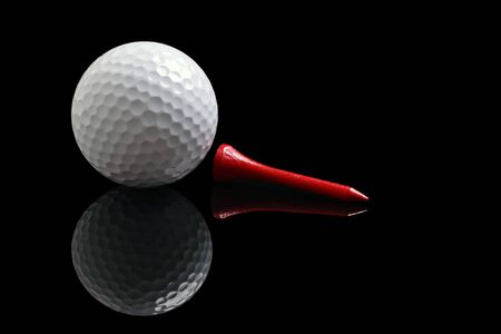 double game: golf ball , tee on black background with reflection