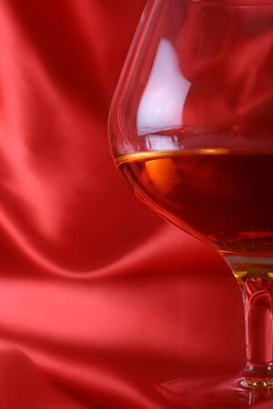 intoxicate: brandy glass on red silk background
