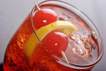 vermouth and soda cocktail with lemon and cherry to garnish