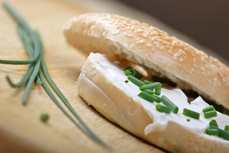 bagel with cream cheese and freshly cut chives photo