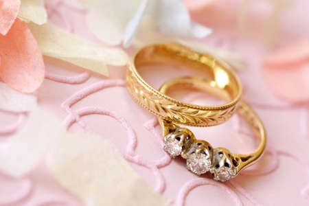 gold wedding ring and engagement ring surrounded by confetti Stock Photo