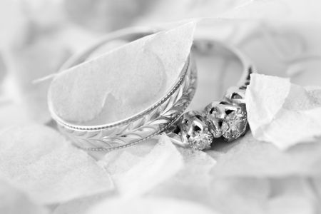 wedding ring and engagement ring surrounded by confetti