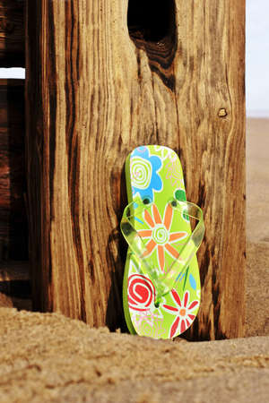 flipflops: trendy bright colored flip flop on a deserted beach Stock Photo