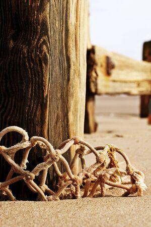 groyne: old weathered and worn beach groyne with abandoned fishing net