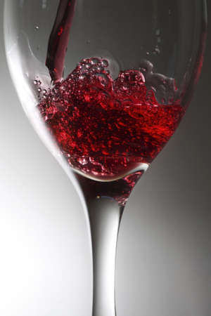 glass of freshly poured red beverage photo