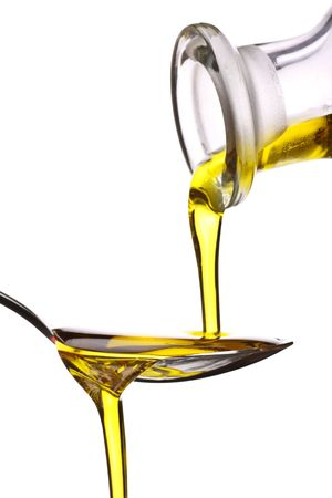 cooking oil: extra virgin olive oil being poured onto a spoon