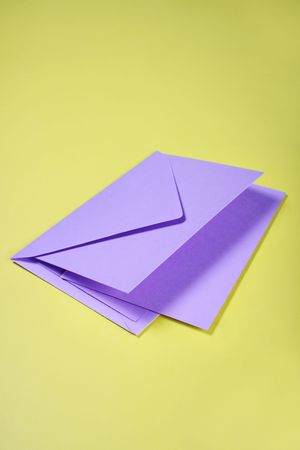 notelet: purple envelope and letter on yellow with space for text Stock Photo