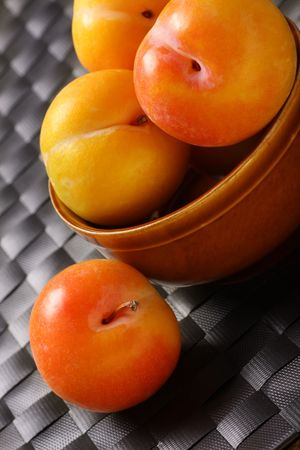 plump ripe fresh plums in a bowl Imagens