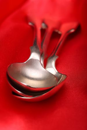 decadent: old silver spoons on a decadent red silk tablecloth