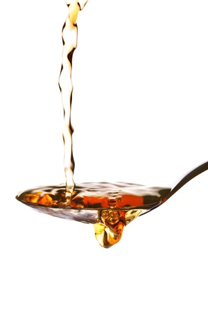 measuring spoon: Malt vinegar being poured onto a measuring spoon, isolated on white Stock Photo