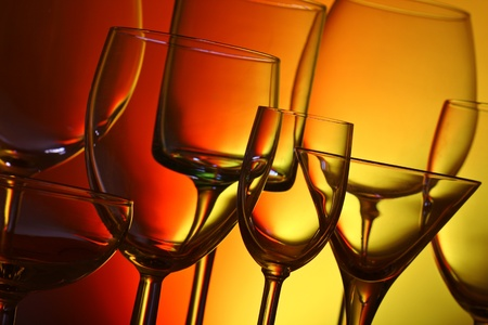 A variety of drinking glasses, backlit with coloured background photo