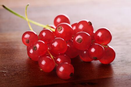 Freshly picked redcurrants placed on wooden serving board